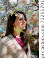 Young woman enjoying the view and the sunlight on her face under Plum tree with blossoms. 71255701