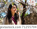 Young woman enjoying the view and the sunlight on her face under Plum tree with blossoms. 71255704
