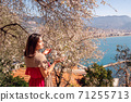 Young woman enjoying the view and the sunlight on her face under Plum tree with blossoms. 71255713