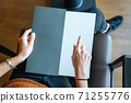 woman is holding and pointing on an empty page as template texture, card, menu or brochure  71255776