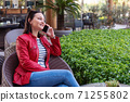 Young woman speak with phone and have a happy face in an elegance cafe. 71255802