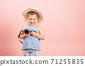 Stylish little girl holding old vintage camera and smiling on pink background 71255835