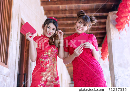 Happy Chinese new year concept. Cheerful smile two young woman wear cheongsam holding red angpao 71257356