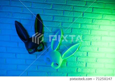 black and white rabbit mask on a white texture wall background in neon green blue 71258147