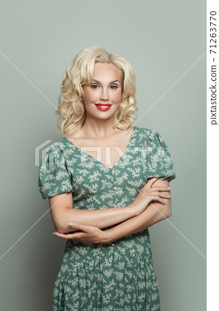 Beautiful woman with makeup and blonde curly hair wearing green dress on light green background 71263770