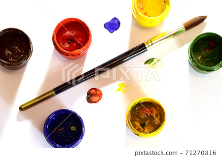 Watercolor paints in jars and a brush on a white table. 71270816