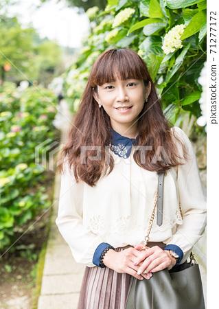 An Asian woman in a hydrangea field. 71277172