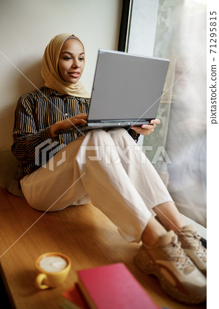 Arab girl sitting on windowsill and using laptop 71295815