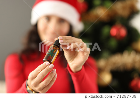 Young woman in santa claus hat holding a bottle with marijuana extract closeup 71297739