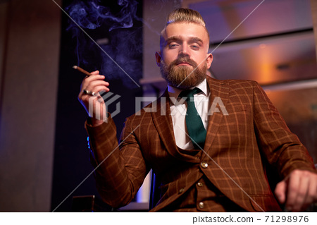 confident wealthy male in suit sit smoking cigar 71298976