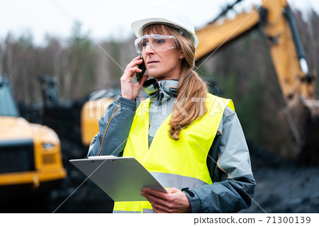 Worker woman in open-cast mining using phone 71300139