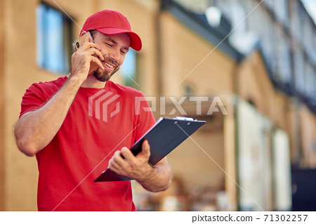 Young smiling caucasian male courier talking on phone 71302257