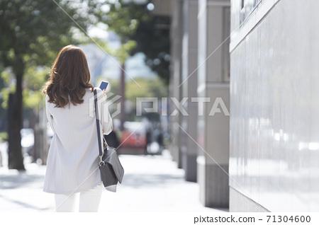 在戶外的智能手機後方的女人 71304600