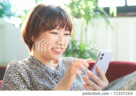 觀看一個智能手機的一位小姐在屋子裡 71307269