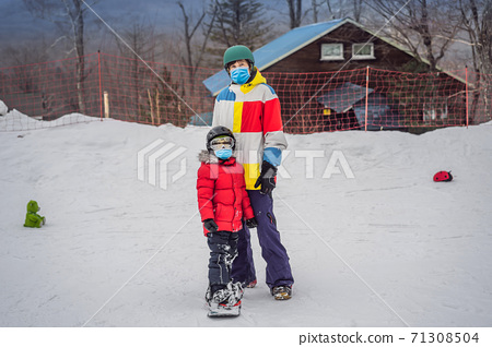 Snowboard instructor teaches a boy to snowboarding wearing a medical mask during COVID-19 coronavirus. Activities for children in winter. Children's winter sport. Lifestyle 71308504