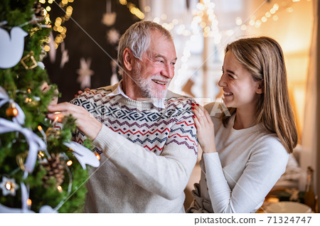 Young woman with senior grandfather indoors at home at Christmas, decorating tree. 71324747