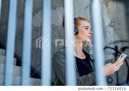 Young woman with red hair outdoors in town, using smartphone and headphones. 71324819