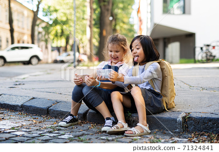 Small girls with smartphones outdoors in town, taking selfie. 71324841