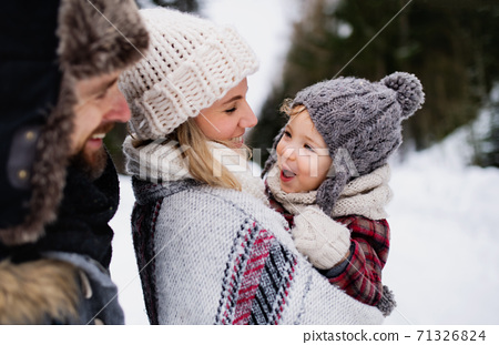 Father and mother with small child in winter nature, standing in the snow. 71326824