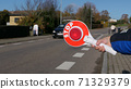 A little boy holds a stop sign at a pedestrian crossing 71329379