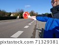 A little boy holds a stop sign at a pedestrian crossing 71329381