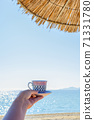 Woman holding cup of coffee at the beach 71331780