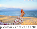 Woman in pink flower dress holding a sea shell over sea and mountains background 71331781