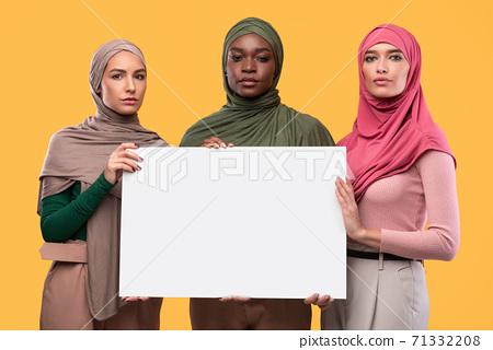 Three Serious Muslim Women Holding Blank Paper Board, Yellow Background 71332208