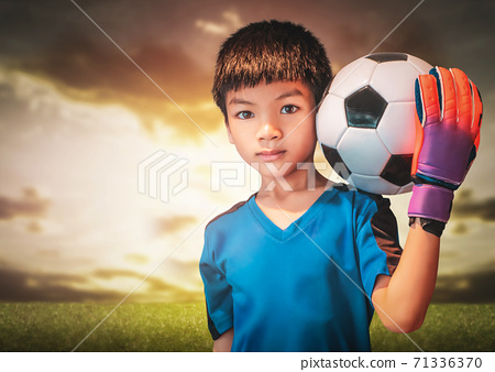 Asian boy is a football goalkeeper wearing gloves and holding a soccer ball with cloud sky background. 71336370