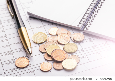 A pile of euro coins on an old black wooden table. Pen, notebook and accounting documents. The concept of the balance of profits and expenses 71339290