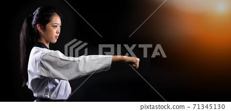 TaeKwonDo Karate teenager athlete kick punch black background isolated 71345130