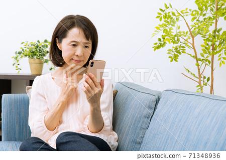 看著智能手機的女人感到驚訝和困擾 71348936