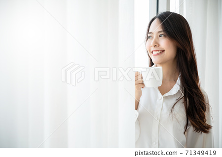 Young asian beautiful woman clothing white pyjamas and drink coffee beside window 71349419
