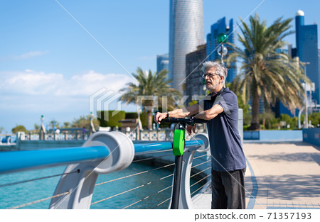 Senior man taking rest while having a ride on electric scooter 71357193