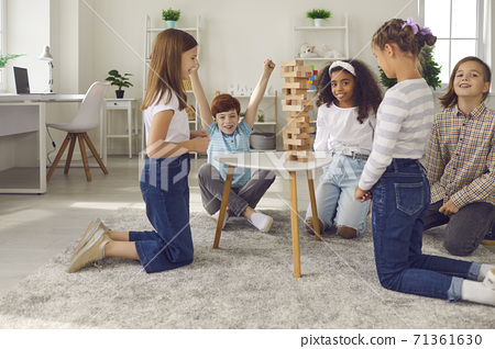 Group of happy kids playing wood block tower stacking game at home or in after school leisure club 71361630
