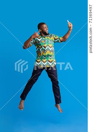Happy black guy in african costume taking selfie 71369497