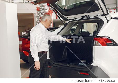 Elegant old man in a car salon 71370688