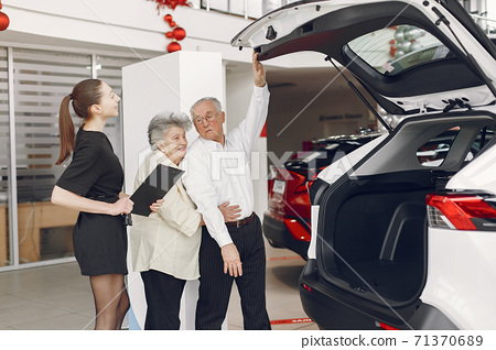 Stylish and elegant old couple in a car salon 71370689