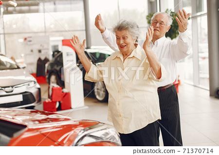 Elegant old couple in a car salon 71370714