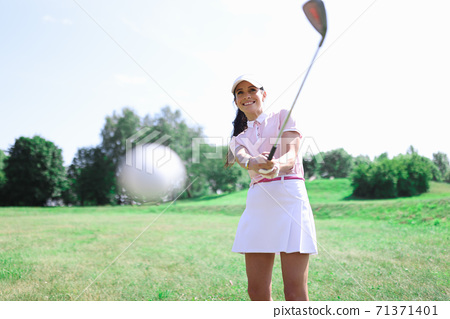 Woman golfer makes a hit with a club on ball. 71371401