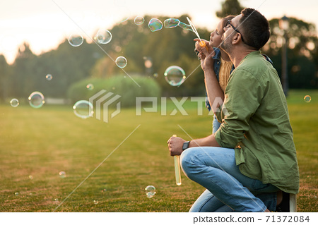Young father and his little girl having fun while blowing soap bubbles on a summer day, daughter and dad spending time together outdoors 71372084