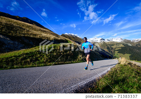 Running on an uphill road in the high mountains 71383337