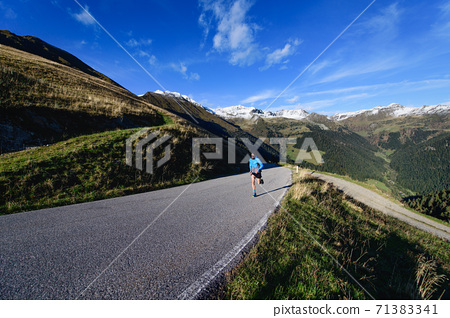 Asphalted mountain road with lonely runner in training 71383341