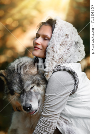 Portrait of a young likable woman with an Alaskan Malamute dog in the autumn forest 71384257