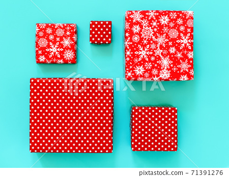 Gift boxes wrapped in red paper on light green background 71391276