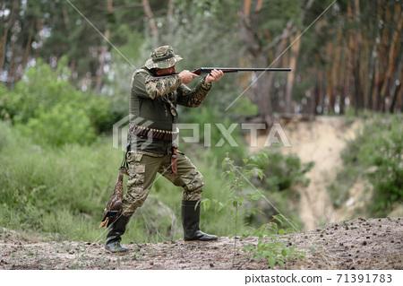 Hunter with Gun at Bird Hunt in Summer Forest. 71391783
