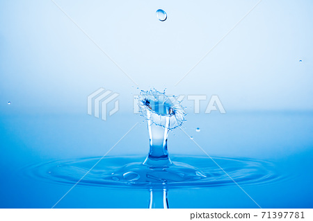 Water drop splashing into blue water surface 71397781