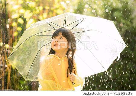 小女孩穿著雨衣,在公園裡在雨中玩 71398238