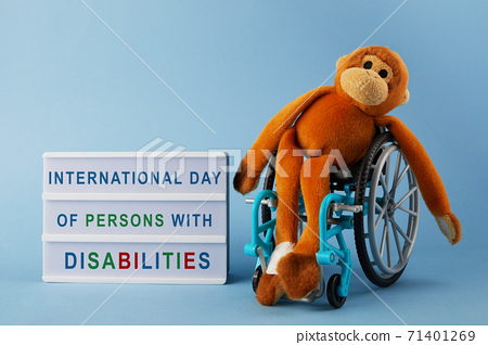 International day of persons with disabilities. Wheelchair wirh toy on blue background. 71401269