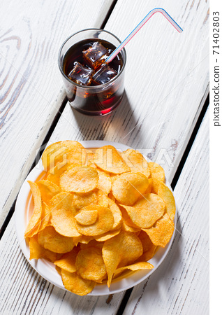 Chips on plate and cola. 71402803